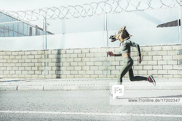 Mature woman in horse mask running on road