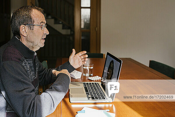 Senior man on video call consultation with female doctor at home during COVID-19