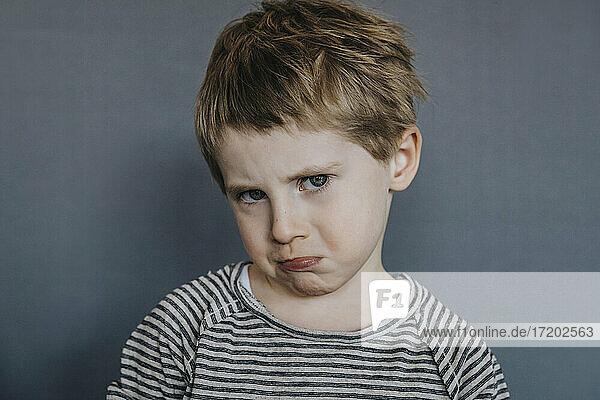 Unschuldiger Junge macht Gesicht auf grauem Hintergrund
