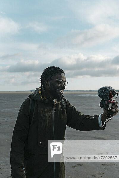 Smiling male vlogger live streaming through camera at beach against sky