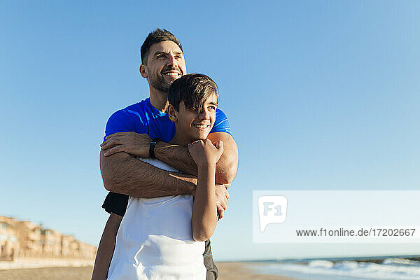 Smiling father embracing son while looking away