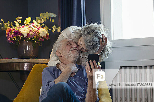 Affectionate woman kissing man while standing behind at home