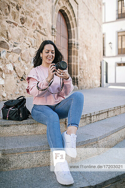 Smiling woman photographing while sitting on staircase against wall