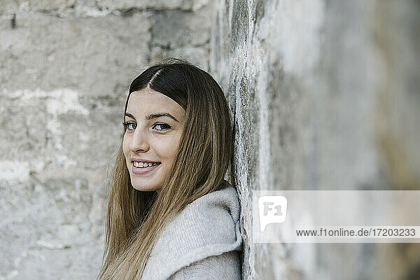 Smiling woman leaning on wall