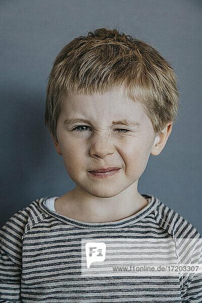 Verspielter Junge zwinkert vor grauem Hintergrund