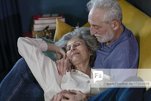 Smiling woman resting on senior man lap at home