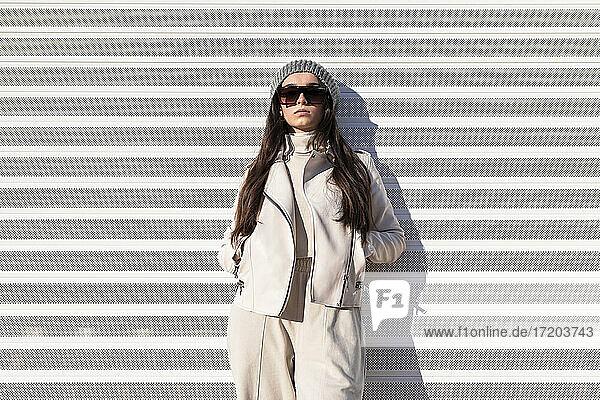 Modisches Teenager-Mädchen mit Händen in den Taschen  das an einer weißen Wand lehnt