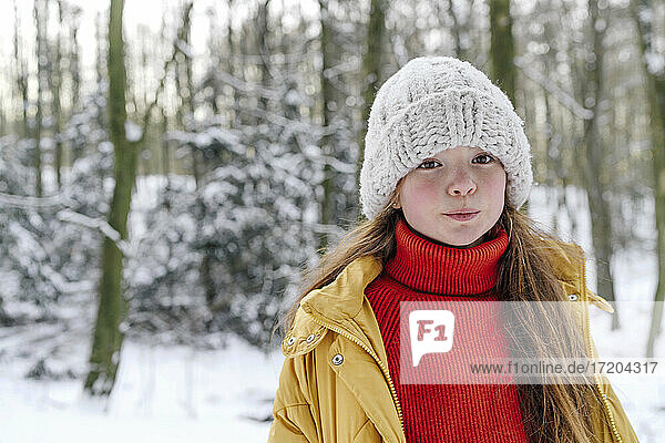 Girl wearing knit hat standing against trees during snow