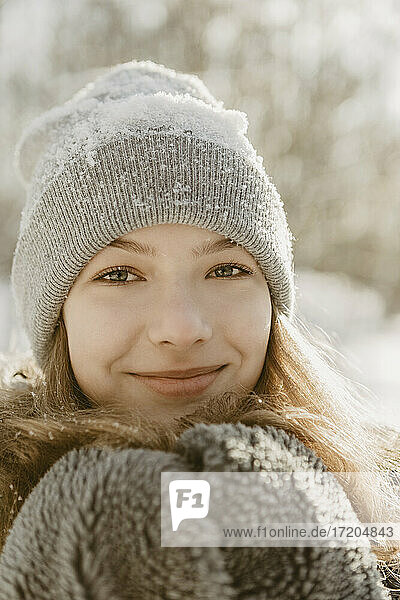 Portrait of beautiful teenage girl wearing knit hat smiling at camera