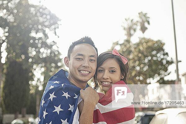 Lächelndes Paar  das in eine amerikanische Flagge eingewickelt im Freien steht
