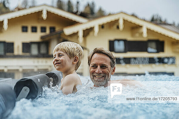 Cheerful son with father enjoying in infinity pool at hotel