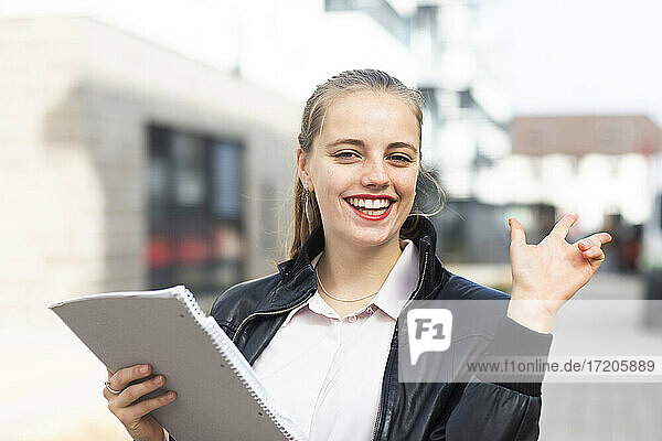 Portrait of young blonde woman standing outdoors with note pad in hand