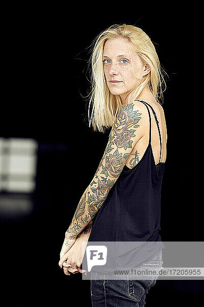 Tattooed woman with hands clasped at parking garage