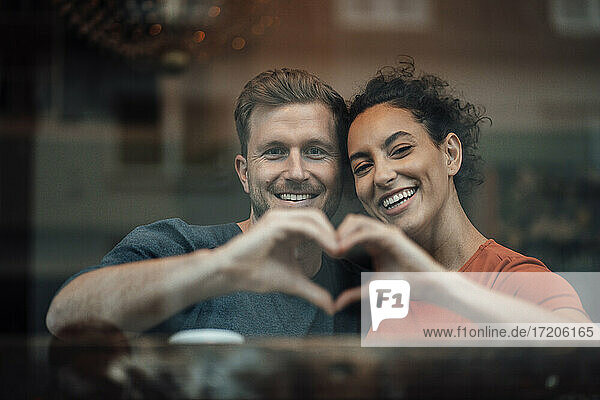 Smiling couple making heart with hand while sitting by cafe window