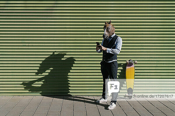 Male entrepreneur in horse mask using mobile phone while standing against wall