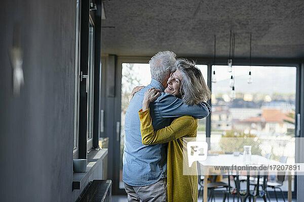 Ältere Frau lächelt  während sie einen Mann zu Hause umarmt