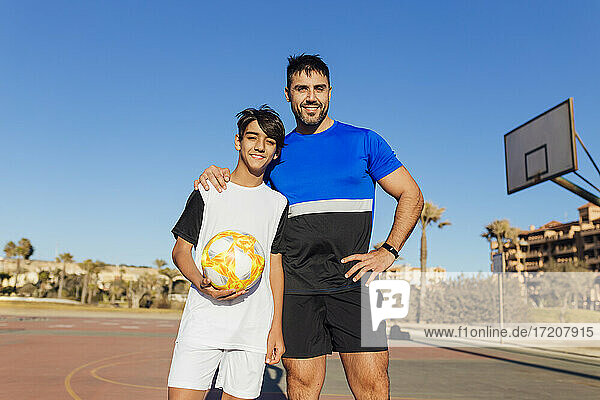 Smiling father with hand on shoulder of son standing on sports court