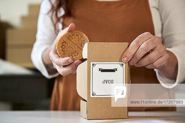 Frau hält Bio-Seife über brauner Schachtel in der Werkstatt Frau hält Bio-Seife über brauner Schachtel in der Werkstatt