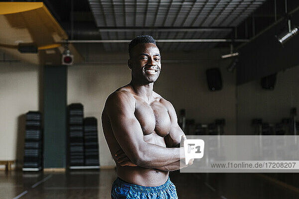 Smiling male athlete standing with arms crossed in health club
