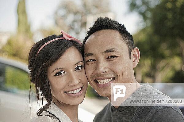 Lächelndes Paar steht Wange an Wange im Freien