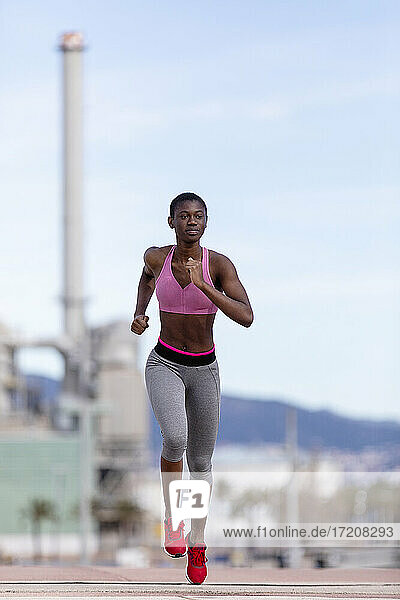 Determined female athlete running on road while looking away