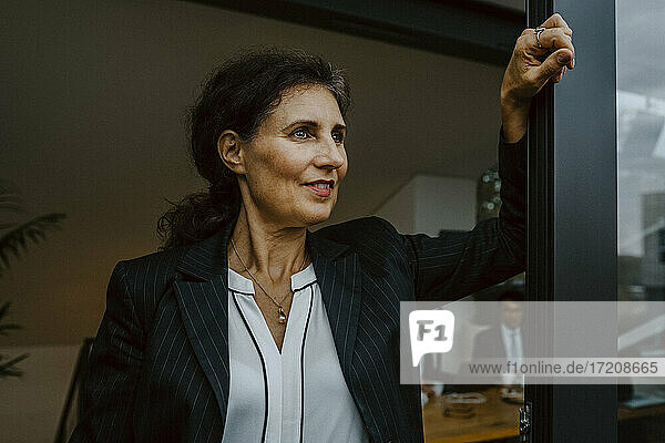 Smiling businesswoman contemplating while leaning on window at office