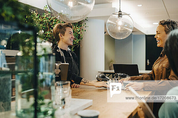 Smiling female customer talking with businesswoman in coffee shop