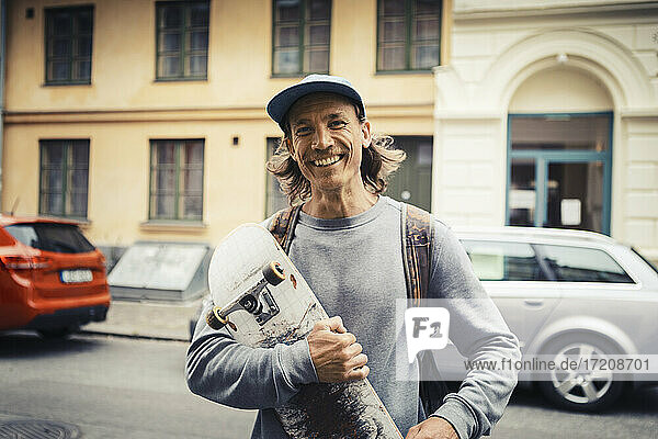 Portrait of man with skateboard standing on street