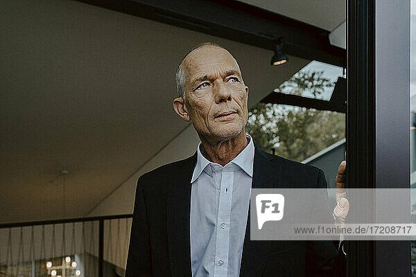 Senior businessman looking away at office