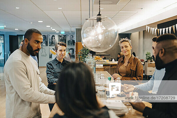 Male and female professionals discussing during meeting at cafeteria in office