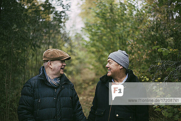 Smiling senior gay couple looking at each other in forest