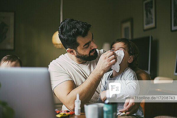 Father blowing nose of son in living room