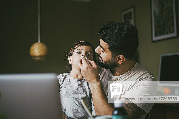 Father giving nasal spray inhaler to son at home
