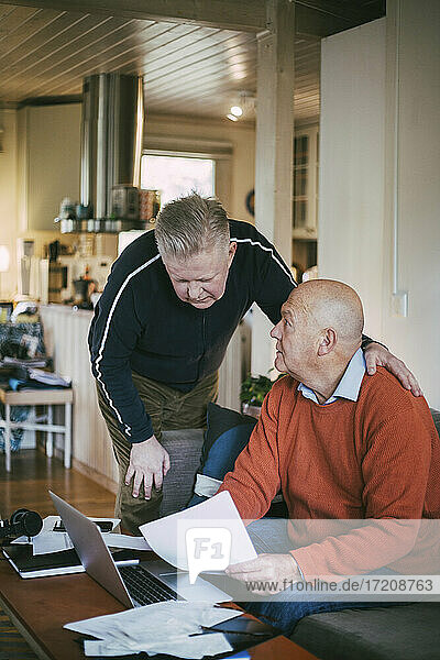 Senior gay couple calculating financial bills in living room at home