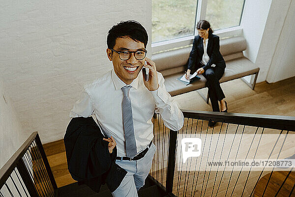 Portrait of smiling businessman talking on smart phone while climbing steps in office