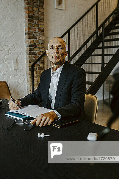 Portrait of confident businessman at table in office