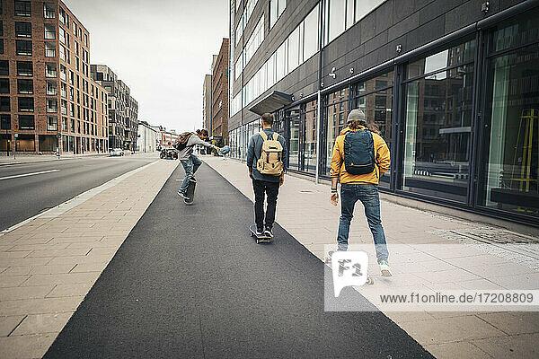 Male friends skating on sidewalk in city