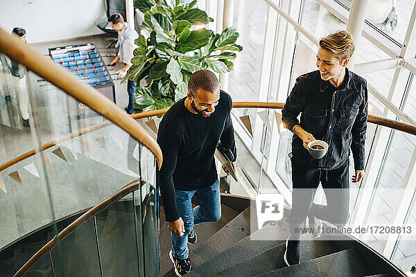 Smiling male and female climbing steps in office