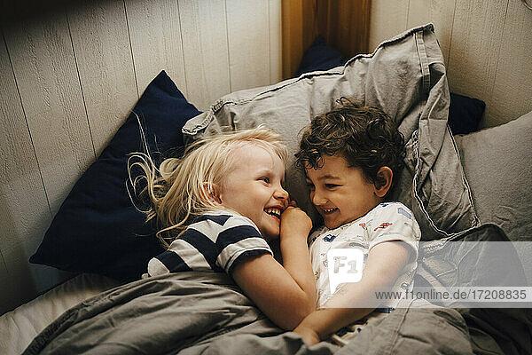 Smiling siblings sleeping in bedroom at night