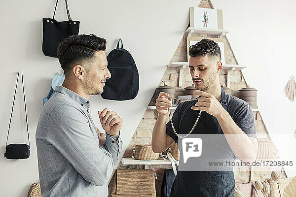 Male owner showing chain to customer in design studio