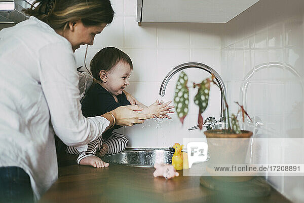 Smiling mother helping baby girl washing hands under sink in kitchen