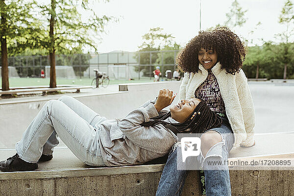 Teenage girl resting head on female friends lap while sitting on retaining at skateboard park