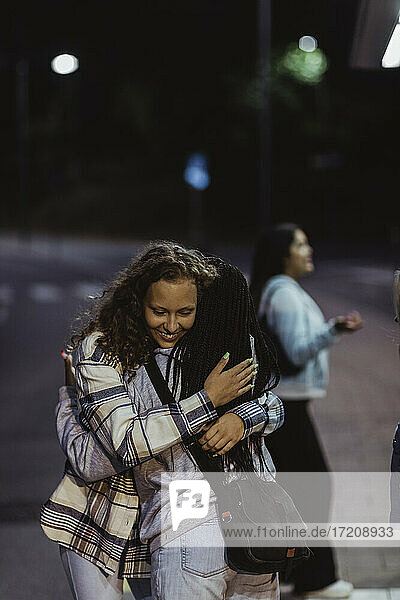 Female friends embracing each other on street at night