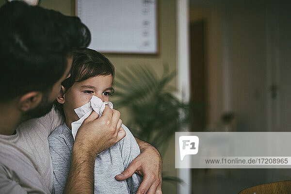 Father blowing nose of sick son at home