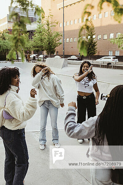 Cheerful female friends dancing at skateboard park in city