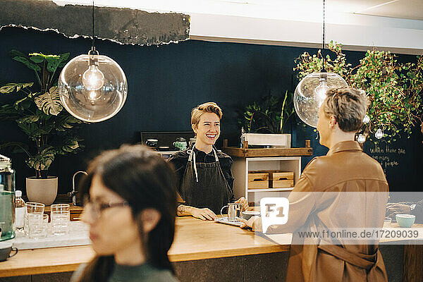 Smiling businesswoman talking with female customer at table in coffee shop