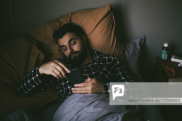 Sick man using smart phone while lying on bed at home
