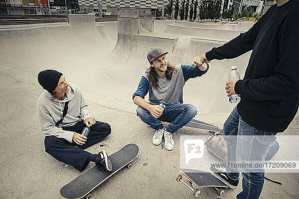 Male friends doing fist bump at skateboard park