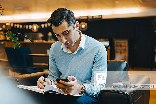 Male entrepreneur with smart phone writing in book at office