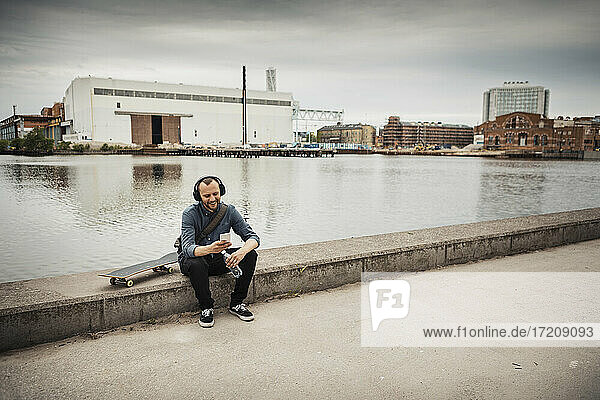 Smiling man using smart phone sitting on retaining wall against canal